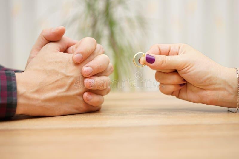Η γυναίκα θέλει να χωρίσει τη σχέση με τον άνδρα και να του δώσει το δαχτυλίδι β στοκ φωτογραφία