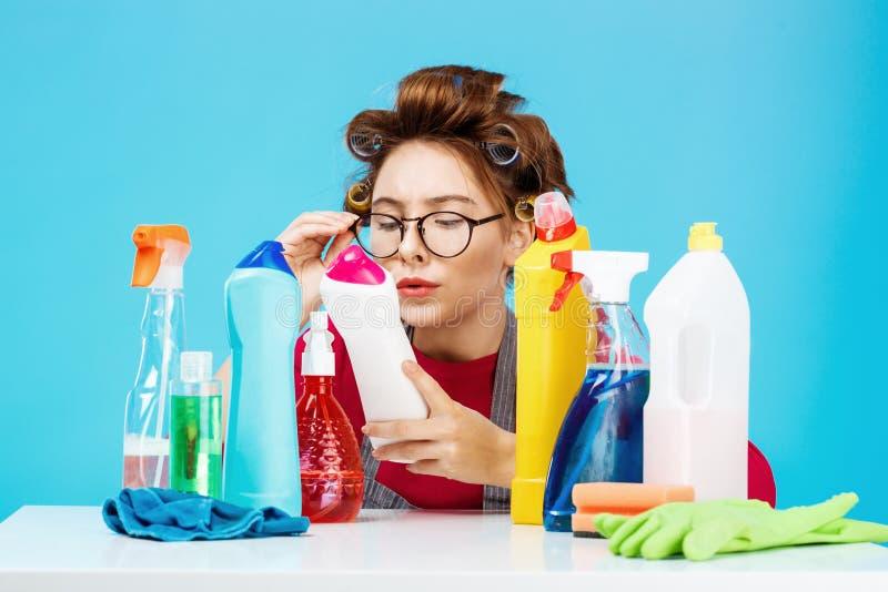 Η γυναίκα διαβάζει τις λεπτομέρειες στο μπουκάλι κάνοντας τα οικιακά, φαίνεται κουρασμένη στοκ εικόνα με δικαίωμα ελεύθερης χρήσης