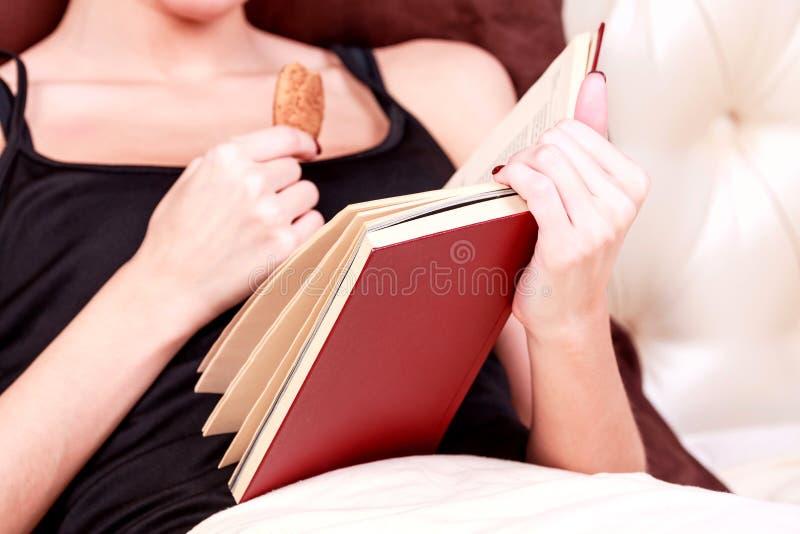 Η γυναίκα διαβάζει το βιβλίο σε ένα κρεβάτι στοκ φωτογραφία