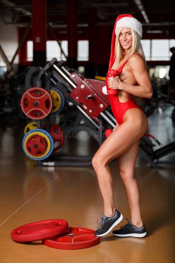 Η γυναίκα ικανότητας, ολόκληρη, σε ένα κόκκινο μαγιό, που φορά ένα καπέλο Santa, στέκεται στην τοποθέτηση γυμναστικής στοκ φωτογραφία
