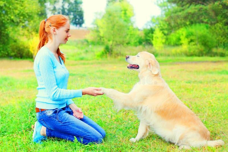 Η γυναίκα ιδιοκτητών εκπαιδεύει το χρυσό Retriever της σκυλί στη χλόη στοκ φωτογραφία