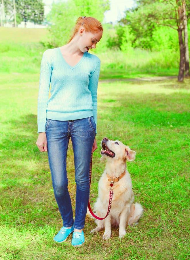 η γυναίκα ιδιοκτητών και το χρυσό Retriever σκυλί είναι εξετάζουν η μια την άλλη περίπατος στοκ εικόνα