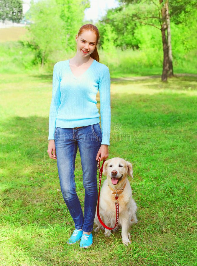 Η γυναίκα ιδιοκτητών με το χρυσό Retriever σκυλί περπατά μαζί στο θερινό πάρκο στοκ εικόνα με δικαίωμα ελεύθερης χρήσης