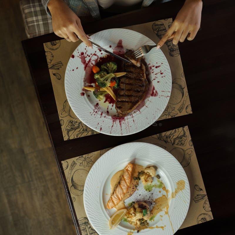 Η γυναίκα κάθεται σε έναν ξύλινο πίνακα σε ένα εστιατόριο και τεμαχίζει τη juicy μπριζόλα στοκ φωτογραφία με δικαίωμα ελεύθερης χρήσης