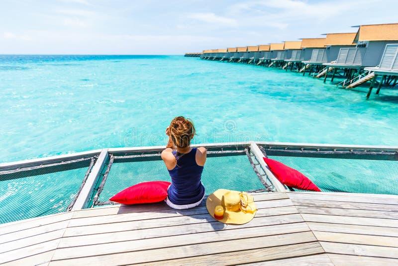 Η γυναίκα κάθεται σε καθαρό πέρα από τη θάλασσα στοκ φωτογραφία