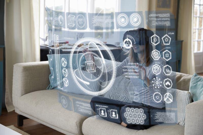 Η γυναίκα κάθεται στον καναπέ που φορά στο σπίτι την κάσκα εικονικής πραγματικότητας στοκ φωτογραφία