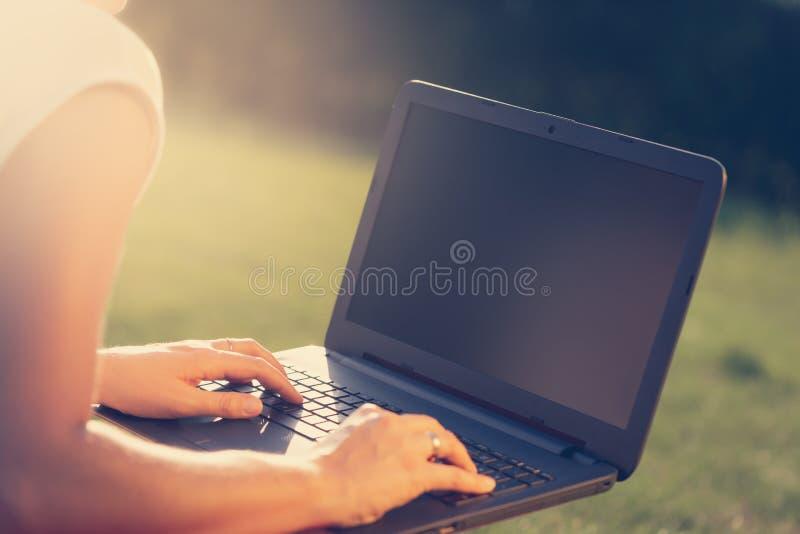Η γυναίκα κάθεται στο κάλυμμα στο πάρκο ή τον κήπο και δακτυλογραφεί στο lap-top της στοκ φωτογραφίες