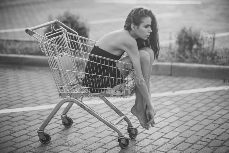 Η γυναίκα κάθεται στο κενό κάρρο αγορών στοκ εικόνες