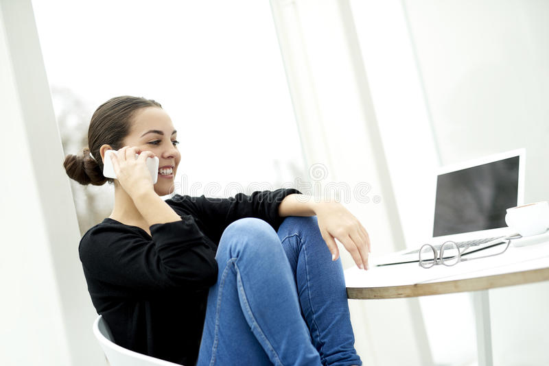 Η γυναίκα κάθισε άνετα στην καρέκλα που μιλά στο τηλέφωνο στοκ εικόνα