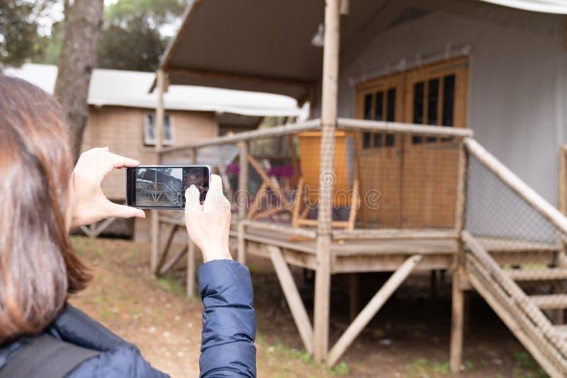 Η γυναίκα κάνει μια εικόνα του ξύλινου εξοχικού σπιτιού ενοικίου της με το τηλέφωνο στοκ φωτογραφία με δικαίωμα ελεύθερης χρήσης