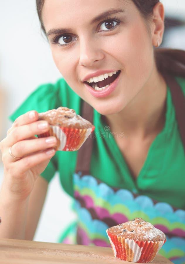 Η γυναίκα κάνει τα κέικ στην κουζίνα στοκ φωτογραφία