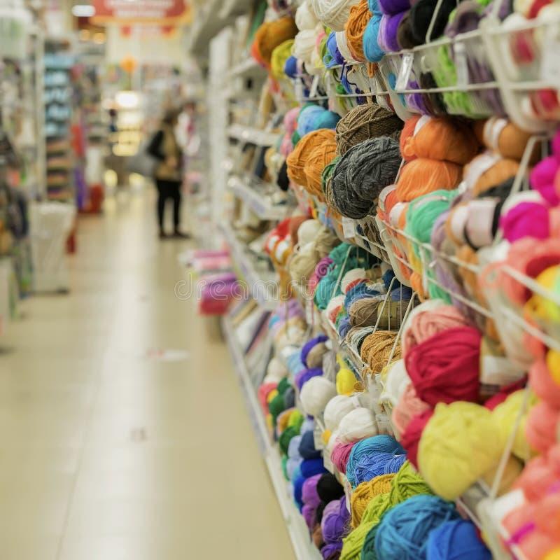 Η γυναίκα κάνει την επιλογή του νήματος για το πλέξιμο στο κατάστημα των αγαθών για τη δημιουργικότητα και τη ραπτική Ράφια στο κ στοκ εικόνες