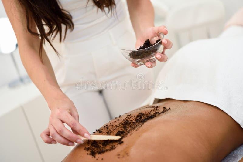 Η γυναίκα καθαρίζει το δέρμα του σώματος με τον καφέ τρίβει στο wellness SPA στοκ φωτογραφία με δικαίωμα ελεύθερης χρήσης