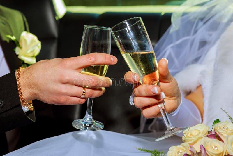 Η γυναίκα και επανδρώνει τα γαμήλια χέρια με τα γυαλιά στοκ εικόνες