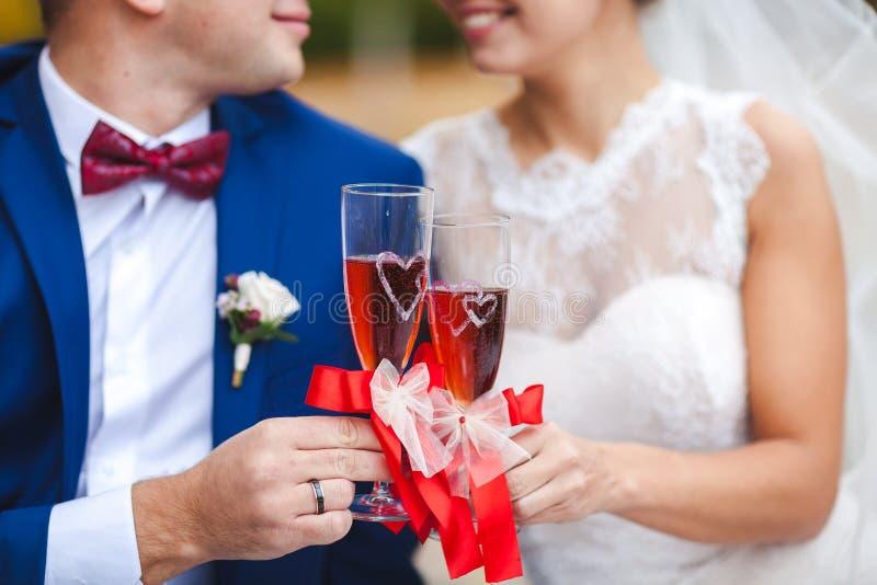 Η γυναίκα και επανδρώνει τα γαμήλια χέρια με το κόκκινο κρασί γυαλιών στοκ φωτογραφία