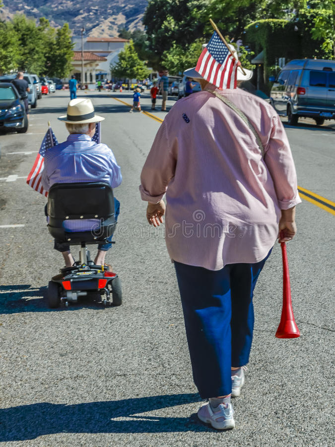 η γυναίκα και ο άνδρας στην καρέκλα ροδών περπατούν από την παρέλαση στοκ φωτογραφία με δικαίωμα ελεύθερης χρήσης