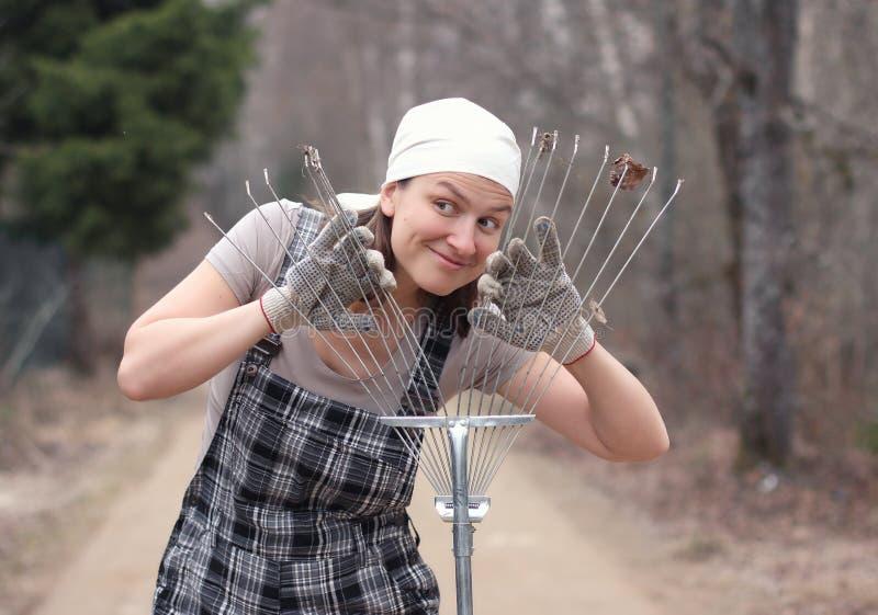 Η γυναίκα κηπουρών ή αγροτών κοιτάζει μέσω της τσουγκράνας Φθινόπωρο ή sprin στοκ εικόνες