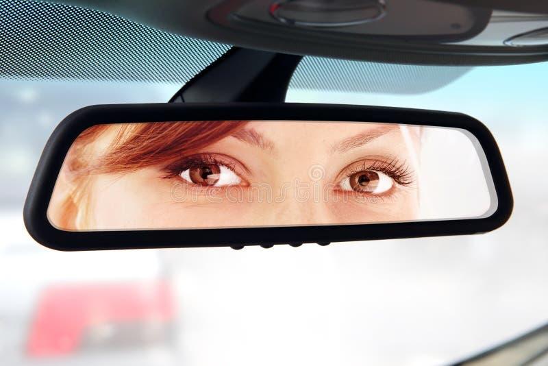 Η γυναίκα κοιτάζει στον οπισθοσκόπο καθρέφτη στοκ εικόνα