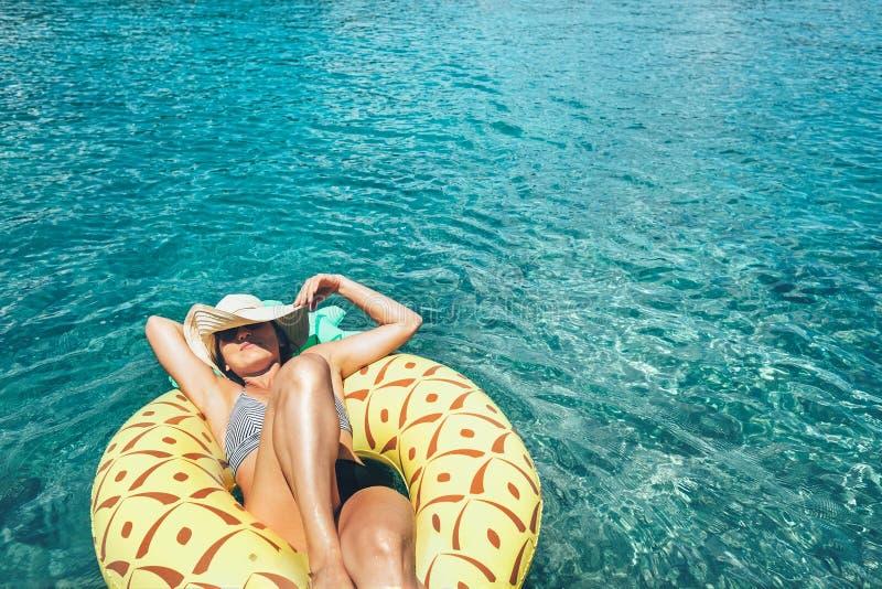 Η γυναίκα κολυμπά στο διογκώσιμο δαχτυλίδι λιμνών ανανά στο κρύσταλλο - το σαφές s στοκ εικόνα
