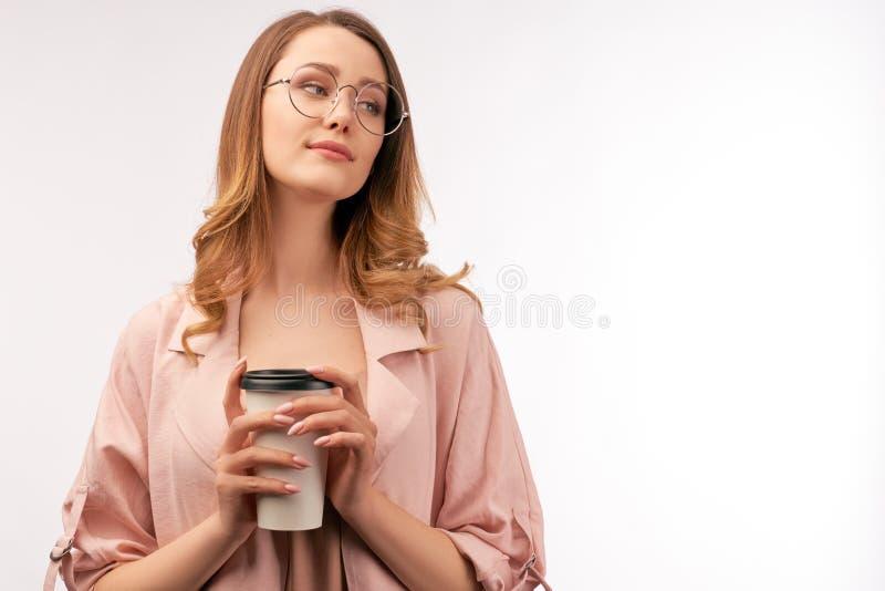 Η γυναίκα κρατά την κούπα καφέ, κοιτάζει κατά μέρος με το χαμόγελο στοκ φωτογραφίες με δικαίωμα ελεύθερης χρήσης