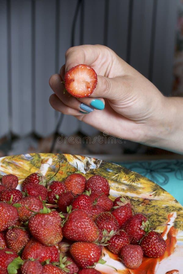 Η γυναίκα κρατά τη φράουλα στο χέρι του Κρατά το χέρι της σε ένα πιάτο των φραουλών στοκ εικόνες