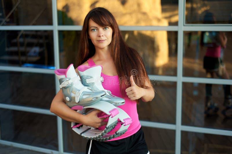 Η γυναίκα κρατά τις μπότες αλμάτων kangoo και παρουσιάζει αντίχειρες στοκ εικόνα