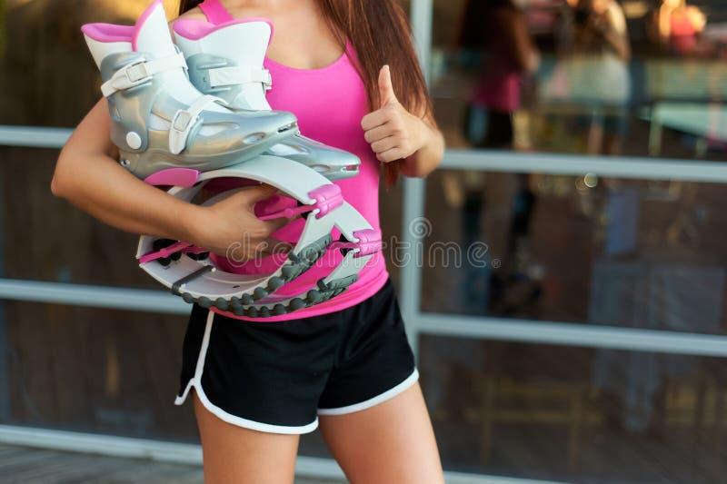 Η γυναίκα κρατά τις ρόδινες μπότες αλμάτων kangoo διαθέσιμες και παρουσιάζει αντίχειρες στοκ εικόνα με δικαίωμα ελεύθερης χρήσης