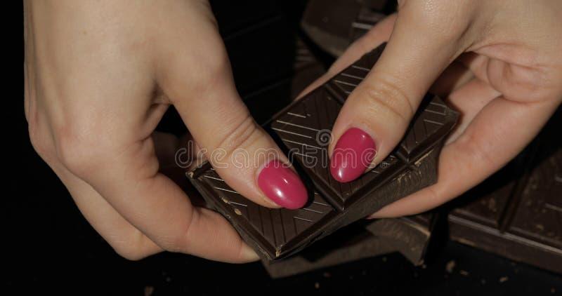 Η γυναίκα κρατά το μαύρο φραγμό σοκολάτας Κινηματογράφηση σε πρώτο πλάνο που πυροβολείται των δάχτυλων γυναικών στοκ φωτογραφία με δικαίωμα ελεύθερης χρήσης