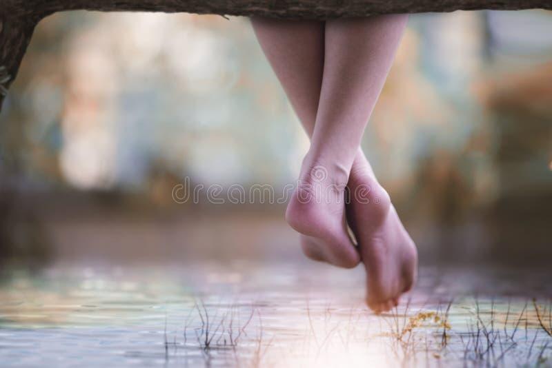 Η γυναίκα κρεμά στο πόδι της σε ένα κούτσουρο επάνω από μια λίμνη στοκ εικόνες με δικαίωμα ελεύθερης χρήσης