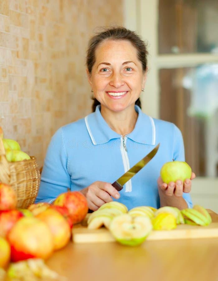 Η γυναίκα κόβει τα μήλα για τη μαρμελάδα μήλων στοκ εικόνες