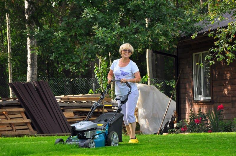 Η γυναίκα κόβει το χορτοτάπητά της με το θεριστή χορτοταπήτων στοκ φωτογραφίες