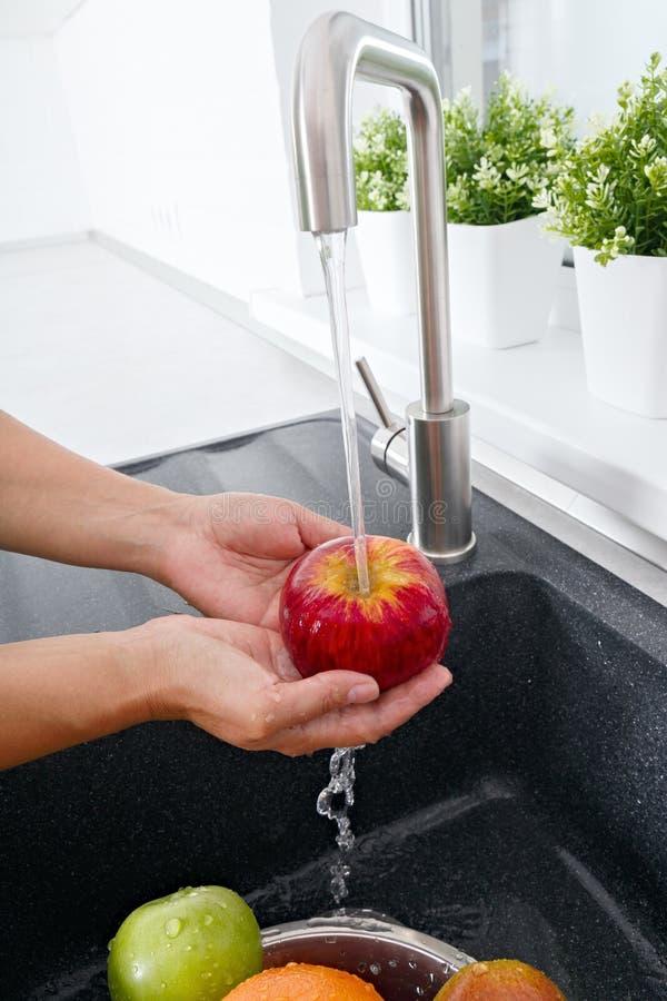 Η γυναίκα μαγείρων πλένει ένα μήλο κάτω από το τρεχούμενο νερό από έναν κρουνό στοκ φωτογραφία