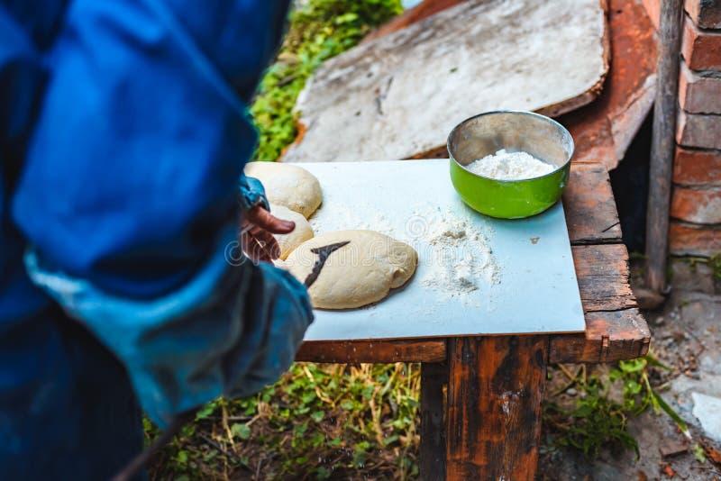 Η γυναίκα μαγειρεύει τη ζύμη για το σπιτικό ψωμί σε υπαίθριο στοκ φωτογραφία με δικαίωμα ελεύθερης χρήσης