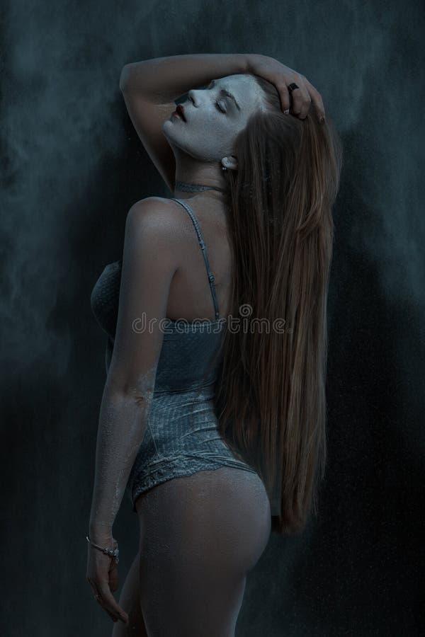 Η γυναίκα με μακρυμάλλη ψεκάζεται με το αλεύρι στοκ εικόνες
