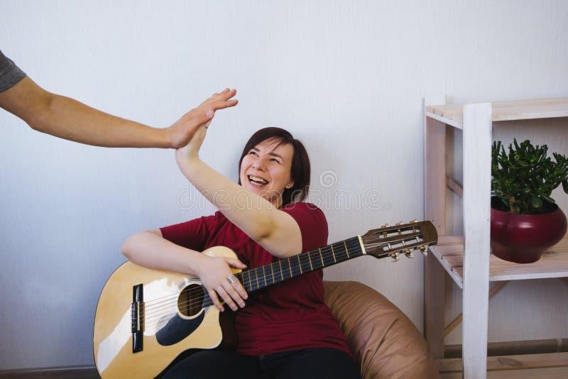 η γυναίκα με μια κιθάρα δίνει πέντε άνδρες από τη ζώνη μουσικής της στοκ φωτογραφίες