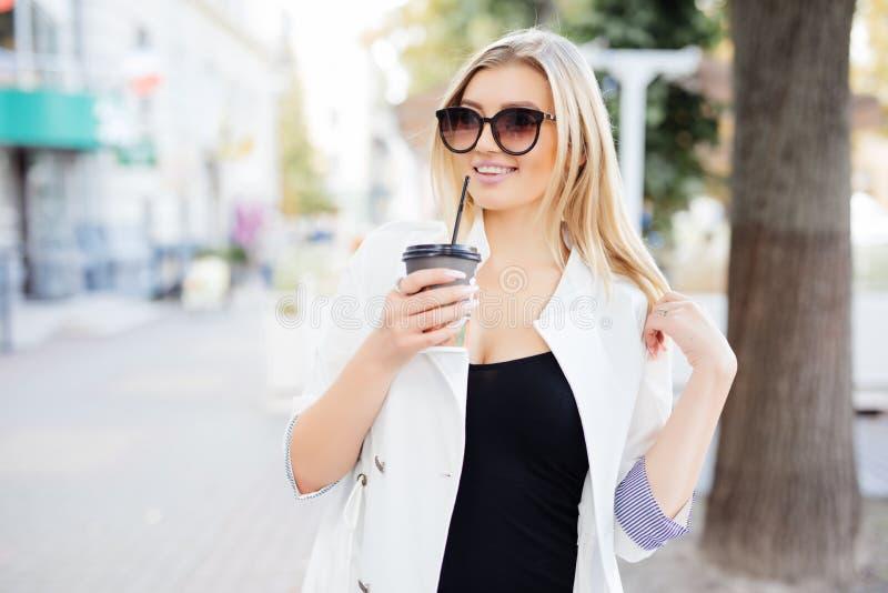 Η γυναίκα με παίρνει μαζί το φλιτζάνι του καφέ ή το τσάι περπατώντας κατά μήκος της οδού πορτρέτο γυναικών υπαίθρια το καλοκαίρι στοκ φωτογραφίες