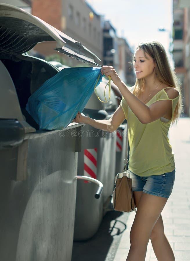 Η γυναίκα με τα απορρίμματα τοποθετεί σε σάκκο κοντά στο δοχείο απορριμάτων στοκ φωτογραφία με δικαίωμα ελεύθερης χρήσης