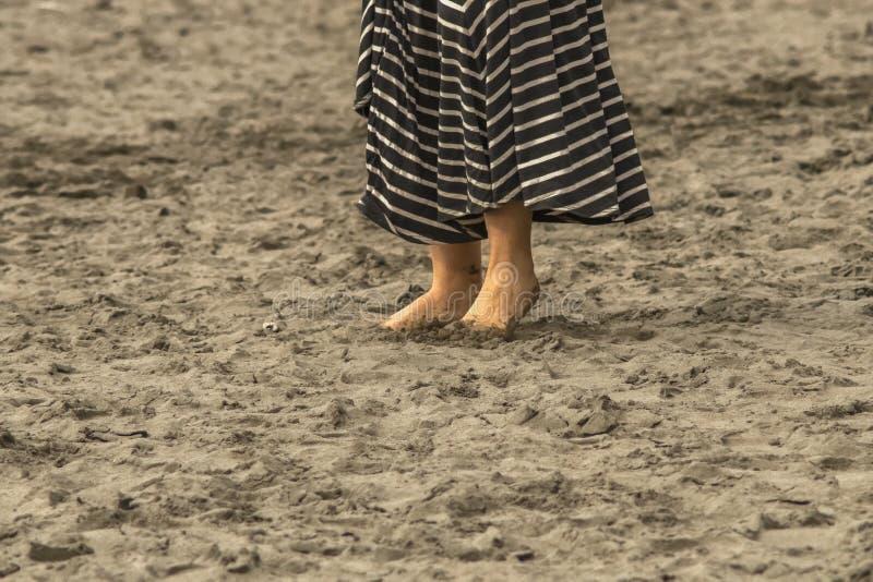 Η γυναίκα με τα βρώμικα πόδια και τα toe έσκαψε στην άμμο στην παραλία με το μεγαλούτσικο φόρεμα - κατώτατο ένα τρίτο του σώματος στοκ εικόνες με δικαίωμα ελεύθερης χρήσης