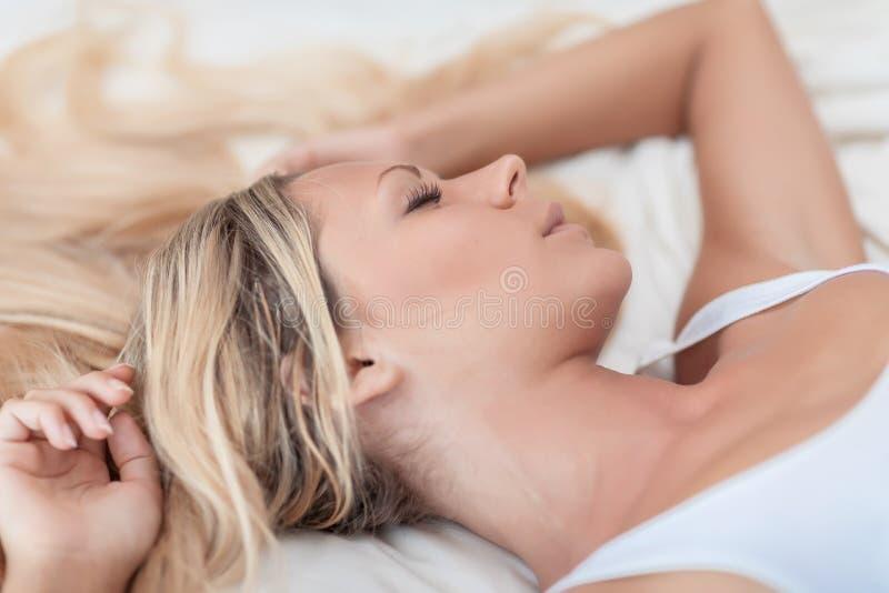 Η γυναίκα με τα μακριά ξανθά μαλλιά στο κρεβάτι δεν θέλει ξυπνήστε το πρωί στοκ φωτογραφίες