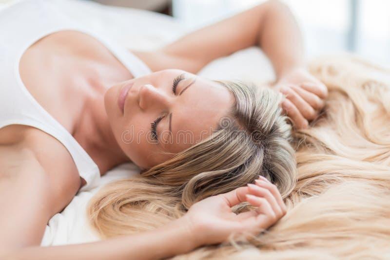 Η γυναίκα με τα μακριά ξανθά μαλλιά στο κρεβάτι δεν θέλει ξυπνήστε το πρωί στοκ φωτογραφία με δικαίωμα ελεύθερης χρήσης