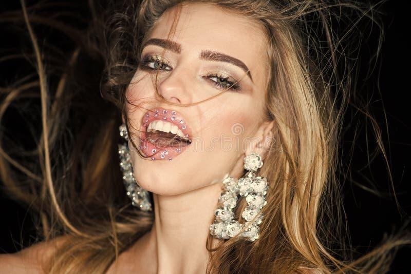 Η γυναίκα με τα μακρυμάλλη και αισθησιακά χείλια φαίνεται ελκυστική Κορίτσι μόδας ομορφιάς με το makeup, κραγιόν με τα rhinestone στοκ εικόνα