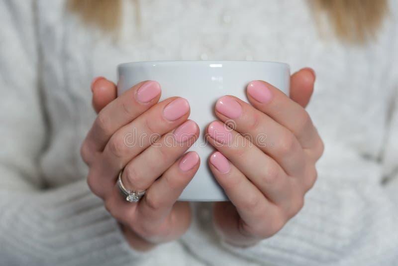 Η γυναίκα με τα ρόδινα καρφιά χρώματος μωρών γυαλίζει το πήκτωμα στα δάχτυλα κρατώντας το φλυτζάνι του τσαγιού στοκ φωτογραφία
