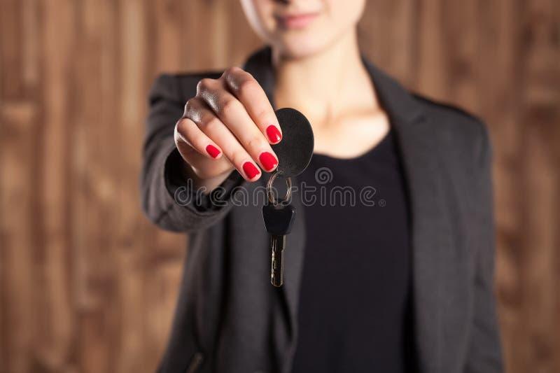 Η γυναίκα με την κόκκινη λάκκα στα καρφιά κρατά τα κλειδιά αυτοκινήτων στο καφετί υπόβαθρο στοκ φωτογραφία με δικαίωμα ελεύθερης χρήσης