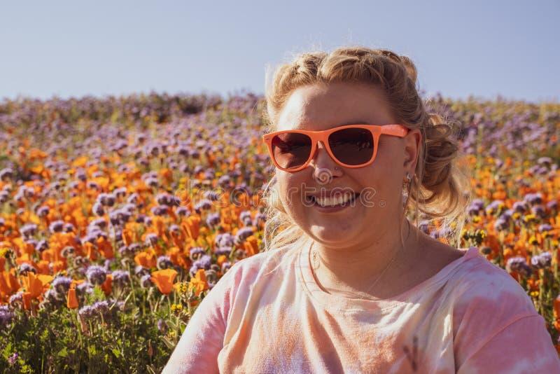 Η γυναίκα με την ξανθά πλεγμένα τρίχα και τα γυαλιά ηλίου θέτει σε έναν τομέα παπαρουνών κατά τη διάρκεια μιας έξοχης άνθισης Ένν στοκ εικόνες