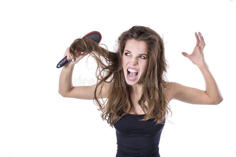 Η γυναίκα με την παχιά καφετιά μπλεγμένη τρίχα προσπαθεί να κτενίσει τις τρίχες αλλά αποτυγχάνει έννοια τρίχας healt στοκ φωτογραφία