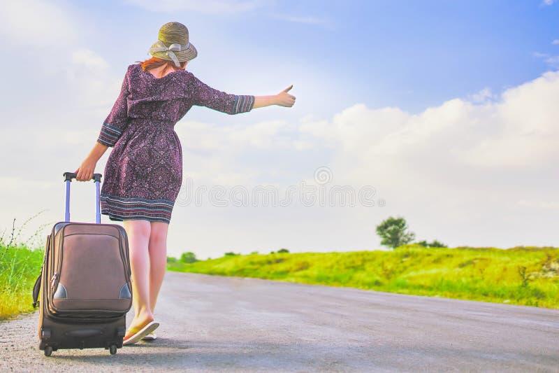 Η γυναίκα με τη βαλίτσα φυλλομετρεί επάνω στοκ εικόνες