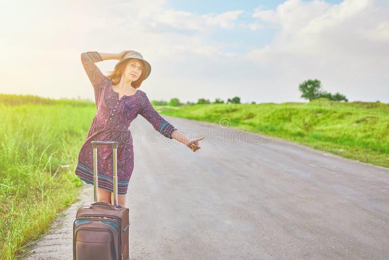 Η γυναίκα με τη βαλίτσα φυλλομετρεί επάνω στοκ φωτογραφία με δικαίωμα ελεύθερης χρήσης