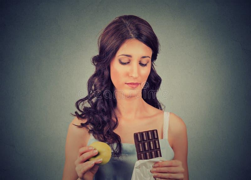 Η γυναίκα με τη σοκολάτα και το μήλο που προσπαθεί να κάνουν μια υγιή επιλογή ελέγχουν το βάρος σωμάτων της περίπου να κάνει δίαι στοκ φωτογραφία με δικαίωμα ελεύθερης χρήσης