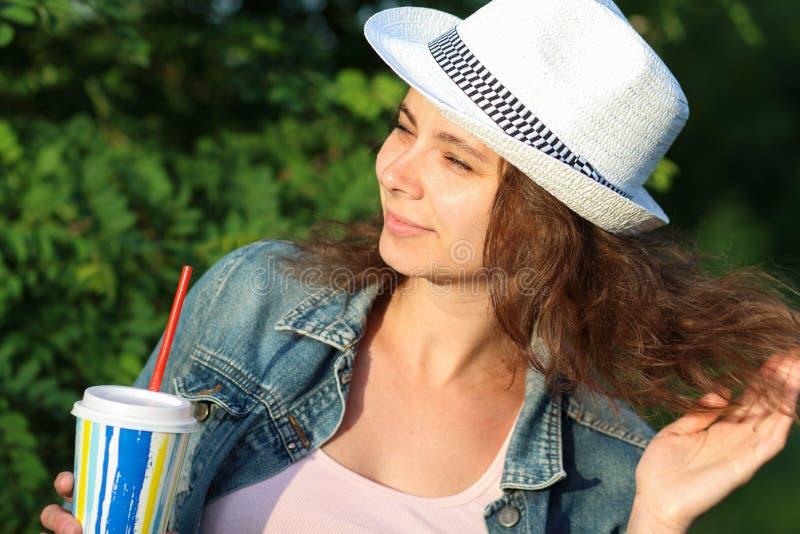 Η γυναίκα με το κοκτέιλ χαλαρώνει στο πάρκο στοκ εικόνες