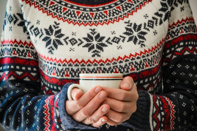 Η γυναίκα με το χειμερινό φόρεμα κρατά μια κούπα καφέ στοκ φωτογραφία με δικαίωμα ελεύθερης χρήσης